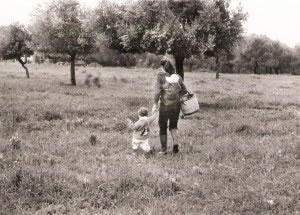 This is a picture taken in 1985 in Bodrum Turkey. Monika is holding her son Derya's hand and has her oldest daughter on her back as they walk to the neighbor's farm to get milk.
